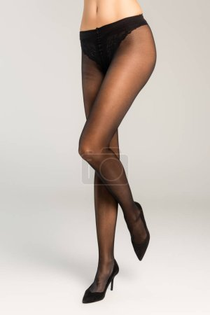 Cropped view of woman standing in black tights and shoes on grey