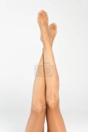 Photo pour Vue recadrée des longues jambes femelles dans l'air avec des collants beiges - image libre de droit