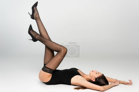 Photo pour Sexy young adult woman with legs in air, wearing bodysuit and lace stockings, lying on grey - image libre de droit