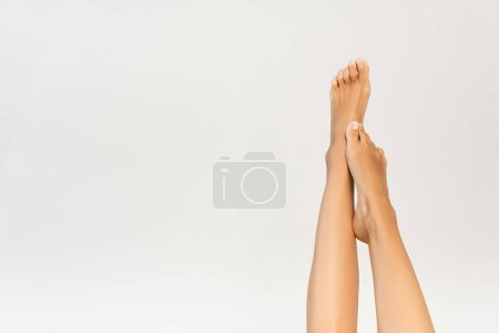 Partial view of woman with smooth legs in air isolated on white