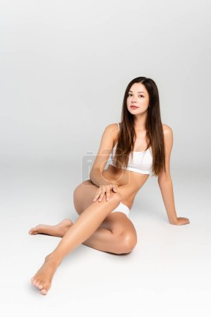 Photo pour Young adult brunette woman in white underwear looking at camera, while sitting on grey - image libre de droit