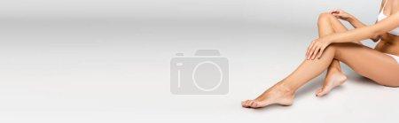 Photo pour Femme tenant les mains sur le genou, assise avec les jambes lisses sur le gris, bannière - image libre de droit