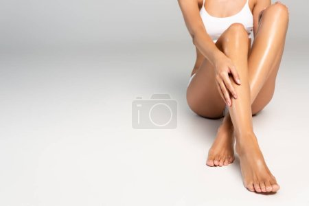 Photo for Cropped view of woman with hand on leg, wearing white underwear, sitting on grey - Royalty Free Image
