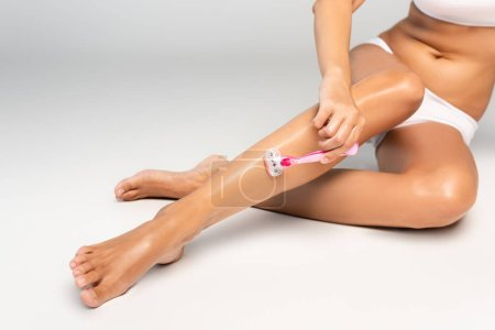 Photo pour Cropped view of woman in white underwear shaving leg with safety razor, while sitting on grey - image libre de droit