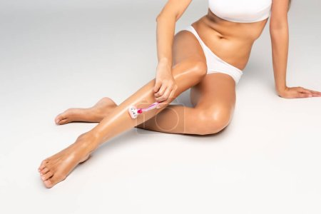Photo pour Vue partielle de la femme portant des sous-vêtements blancs et une jambe à raser avec un rasoir de sécurité, tout en s'appuyant sur le sol avec la main sur le gris - image libre de droit