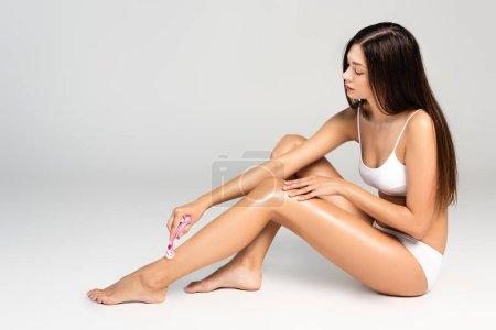 Photo pour Jeune femme adulte portant des sous-vêtements blancs et la jambe de rasage avec rasoir de sécurité sur gris - image libre de droit