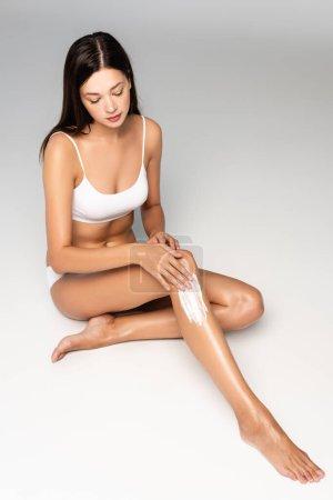 Photo pour Brunette femme en sous-vêtements blancs appliquer crème sur la jambe sur gris - image libre de droit