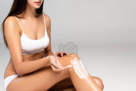 Photo pour Vue recadrée de la femme avec crème cosmétique sur la main et la jambe, portant des sous-vêtements blancs sur le gris - image libre de droit