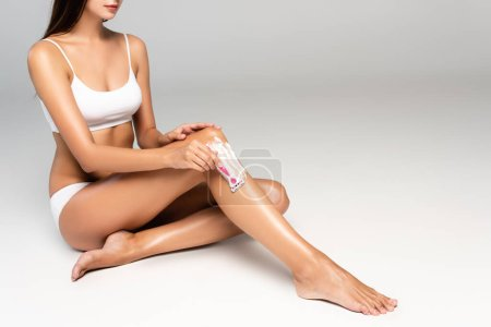 Photo for Cropped view of young adult woman shaving leg with safety razor using cream on grey - Royalty Free Image