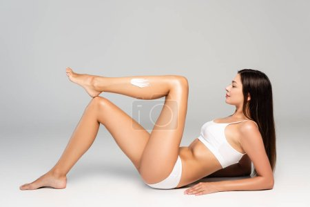Photo pour Side view of brunette woman with cosmetic cream on leg, wearing white underwear, while leaning on grey - image libre de droit