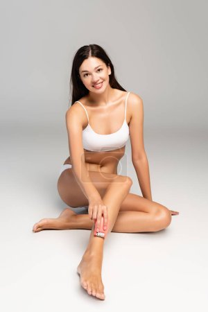 Photo pour Smiling young adult woman in white underwear shaving leg with epilator, while looking at camera on grey - image libre de droit