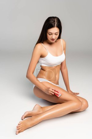 Photo pour Young adult woman in white underwear shaving leg with pink epilator, while sitting on grey - image libre de droit