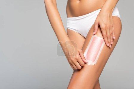 Photo pour Vue recadrée de la femme en culotte blanche jambe de rasage avec bande de cire isolée sur gris - image libre de droit