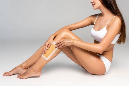 Photo pour Vue recadrée de la jeune femme adulte en sous-vêtements blancs appliquant une bande de cire sur la jambe sur gris - image libre de droit