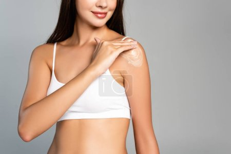 Cropped view of positive woman in white underwear applying cream on shoulder isolated on grey