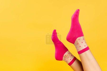Photo pour Vue recadrée des jambes féminines en chaussettes roses isolées sur jaune - image libre de droit