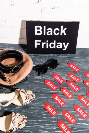 shoes, sunglasses, beret and belt near board with black friday and tags with sale lettering on surface
