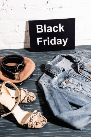 Photo pour Chaussures, béret et ceinture près de la planche avec lettrage noir vendredi et veste en denim - image libre de droit