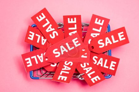 top view of tags with sale lettering in shopping basket on pink, black friday concept