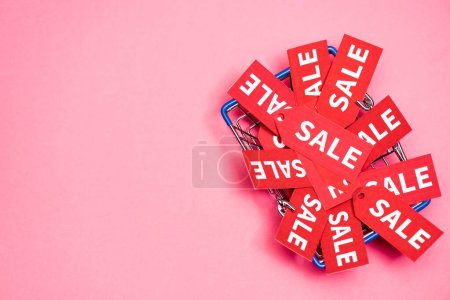 Photo for Top view of sale tags in shopping basket on pink, black friday concept - Royalty Free Image
