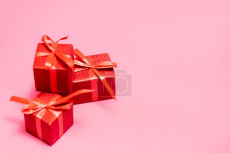 selective focus of red gift boxes on pink, black friday concept