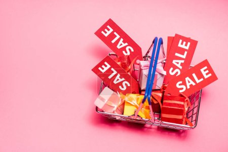 top view of shopping basket with presents and sale tags on pink