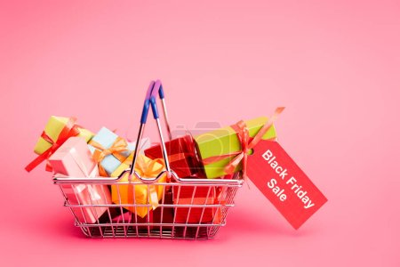shopping basket with presents and red tag with lettering on pink, black friday concept