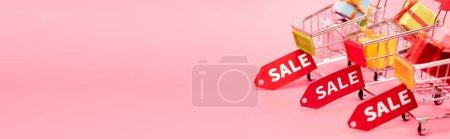 Photo pour Plan panoramique des cadeaux dans les chariots avec des étiquettes de vente sur rose, concept vendredi noir - image libre de droit