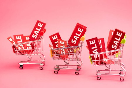red tags with sale lettering in shopping carts on pink