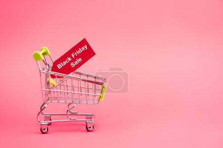 Photo pour Étiquette rouge avec noir vendredi vente lettrage dans le panier sur rose - image libre de droit