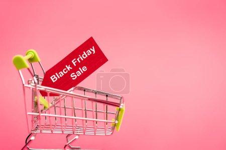 Photo pour Étiquette rouge avec noir vendredi vente lettrage dans le chariot d'achat sur rose - image libre de droit