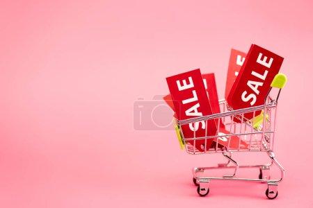 Photo pour Étiquettes rouges avec noir vendredi vente lettrage dans le chariot d'achat sur rose - image libre de droit