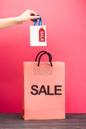 cropped view of woman holding small shopping bag with sale tag near paper package on pink, black friday concept