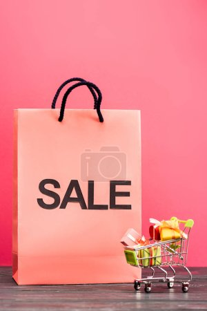 shopping bag with sale lettering near small trolley with gifts on pink, black friday concept