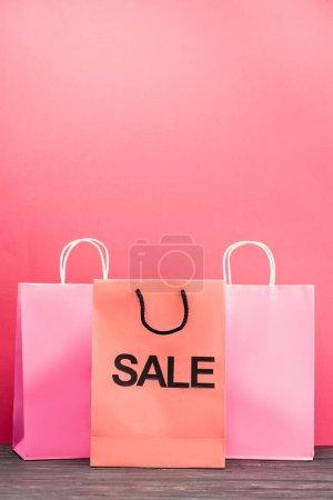 Photo pour Sac à provisions avec vente lettrage près de paquets de papier sur rose, concept vendredi noir - image libre de droit