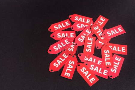 red labels with sale lettering on black background with copy space
