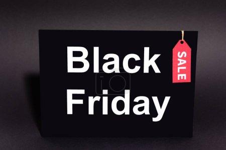plaque avec lettrage noir vendredi et étiquette de vente sur fond sombre