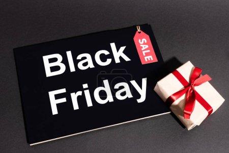 Photo pour Vue du dessus de la boîte cadeau avec ruban et étiquette de vente près de placard noir vendredi sur fond sombre - image libre de droit