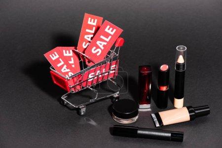 Photo pour Chariot de jouets avec étiquettes de vente près de cosmétiques décoratifs sur fond sombre, concept de vendredi noir - image libre de droit