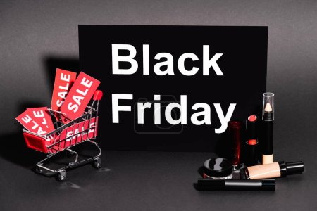 placard with black friday lettering and toy cart with sale tags near decorative cosmetics on dark background