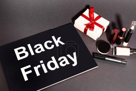 Photo pour Vue grand angle de la plaque avec lettrage noir vendredi et cadeau près des cosmétiques décoratifs sur fond sombre - image libre de droit