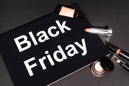 Photo pour Vue grand angle de la plaque avec lettrage noir vendredi près des cosmétiques décoratifs sur fond sombre - image libre de droit