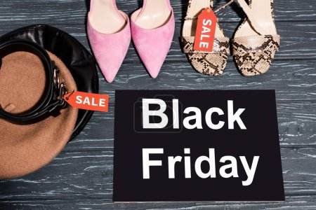 Photo for Top view of trendy shoes near board with black friday lettering, beret and belt on wooden surface - Royalty Free Image