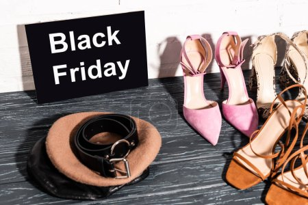 Photo for Trendy shoes near board with black friday lettering, beret and belt on wooden surface - Royalty Free Image