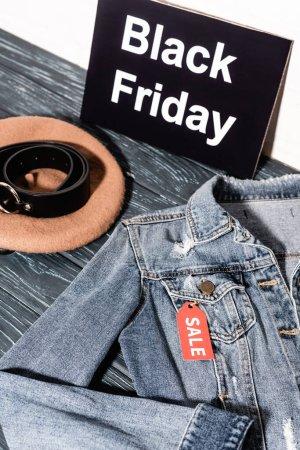 Photo pour Veste en denim bleu près de la plaque avec lettrage noir vendredi, béret et ceinture - image libre de droit
