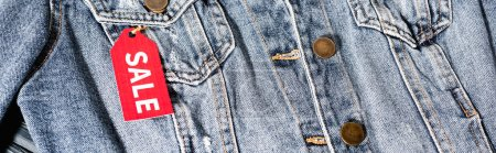 close up of red sale tag on blue denim jacket, panoramic crop