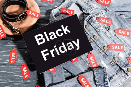 top view of placard with black friday lettering on denim jacket near beret and belt