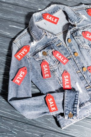 top view of red sale tags on blue denim jacket, black friday concept