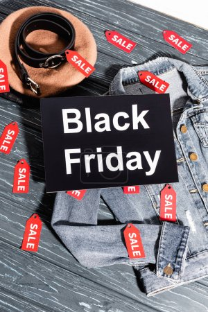 top view of placard with black friday lettering on blue denim jacket near beret and belt