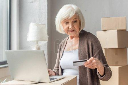 seniorka dokonująca zakupów online kartą kredytową i laptopem